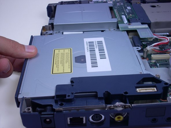 Usning your fingers, slide the optical drive out of the laptop, towards you, and lift it out.