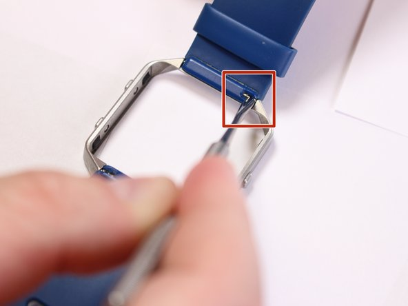 Locate the metal pin behind the wristband located on the edge of metal ring.