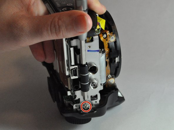 Image 1/2: Remove the two 5.0 mm Phillips #000 screws. One is beneath the function wheel, and one is beneath the shutter button.