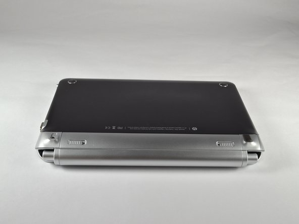 Image 1/1: Close the laptop and turn it over, so that the underside is up and the silver battery bay is facing towards you.