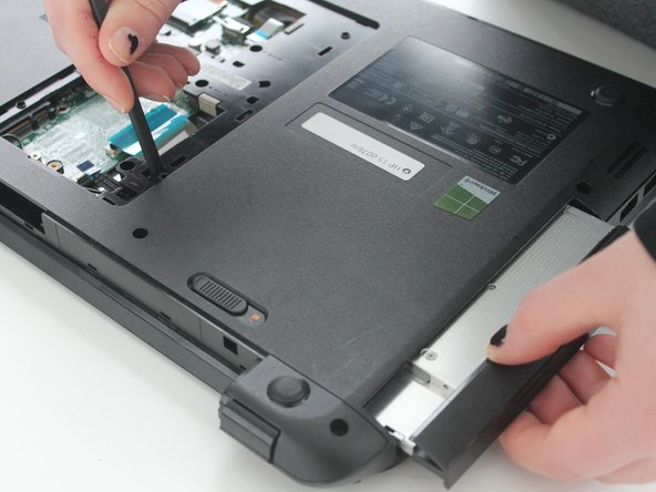 Take the DVD drive in one hand, and using the plastic spludger, push the tab down, and out.