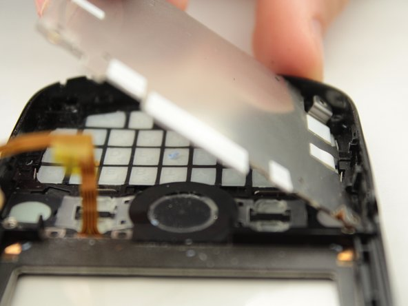 The metal plate should now be loose enough to where one can remove the metal plate with either the plastic opening tool or with one's hands. Remove the metal plate and the keyboard beneath it can be easily removed.