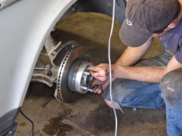Place the wheel adapter over the existing wheel lugs, then install and hand-tighten the provided lug nuts.