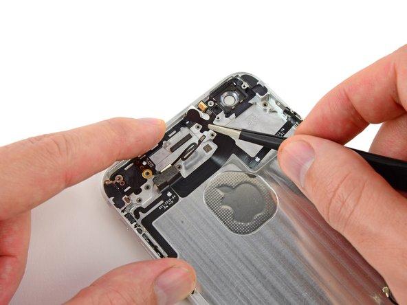 Continuez à décoller doucement la nappe du bouton de marche de la coque arrière et retirez-la de l'iPhone.