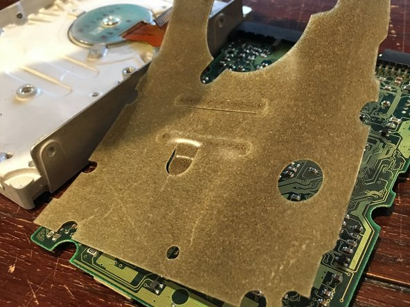 Image 3/3: Pull off the PCB from the back of the hard drive and remove the protective foam sheet from the back of the board.