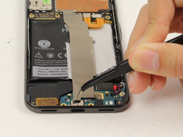 Use tweezers to lift up the silver strip  at the top of the daughterboard, and peel it back to expose the connector underneath.