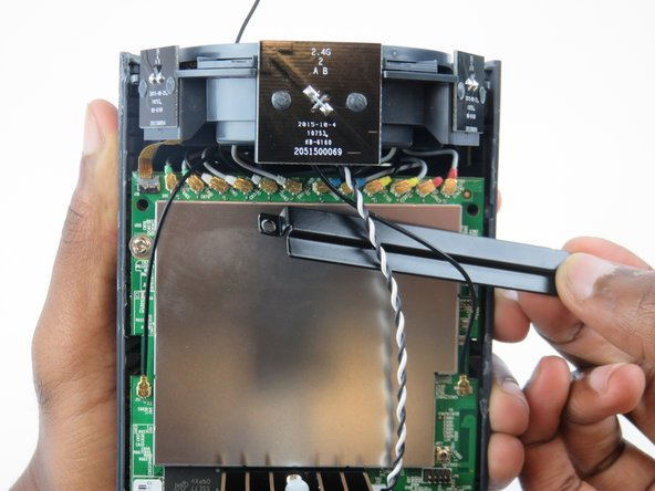 Image 1/2: Using tweezers, gently disconnect each of the 12 wire connections, attached to the top of the motherboard.