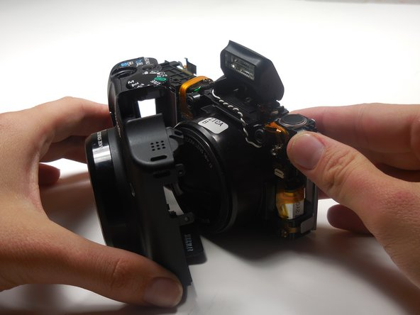 Use your hands to gently separate the front panel from the camera.