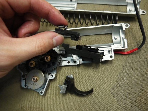 Image 1/3: Remove the three gears and the anti-reversal latch. Be careful not to misplace any of the shims or bushings, or the anti-reversal latch spring.