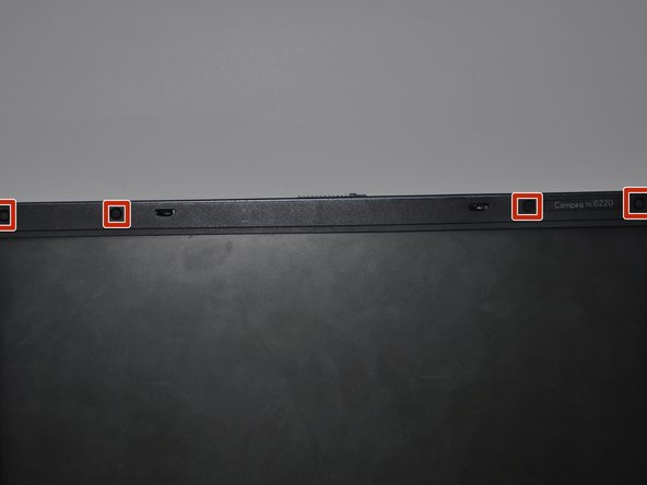 Using a small spudger, remove the four black plastic covers from above the monitor, revealing screws underneath.