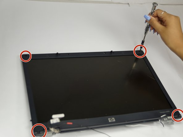Image 1/1: The laptop may have rubber covers over the screws,. Remove them using a pointed tool to pry them out.