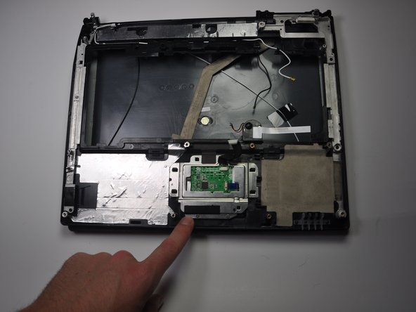 Find the green chip encased by an aluminum frame on the underside of the plastic panel that was removed last in the computer disassembly guide.