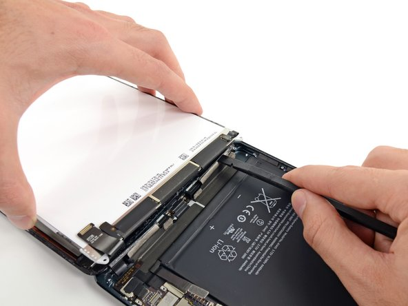 Insert the flat end of a spudger between the LCD frame and tape, and slide outward while gently lifting up on the LCD.