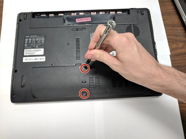 Remove two screws to take the cover off of the bottom of the laptop.