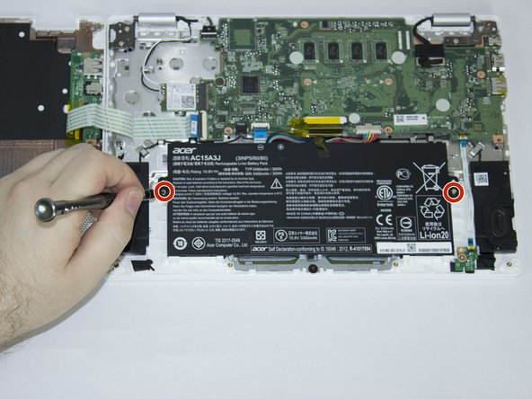 Image 1/1: Unscrew the two screws holding the battery in place. There is one on each side of the battery.