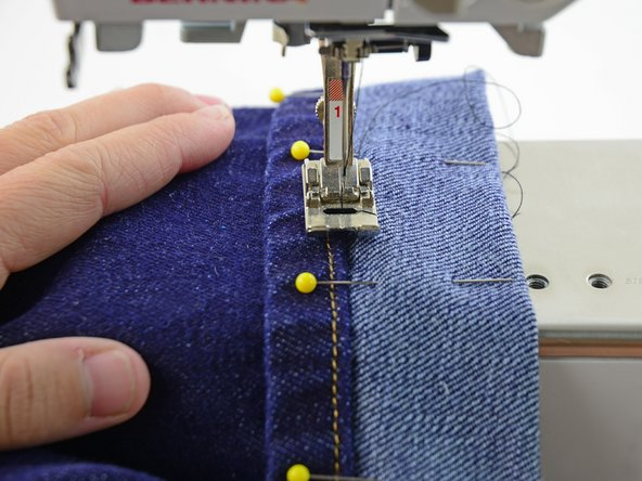 Align the center of the presser foot (and needle) with the edge of the hem on the jeans.
