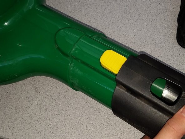Firmly press the yellow button and slide the blower nozzle off.