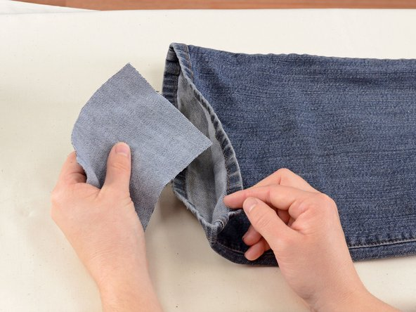Take a scrap of denim and place it inside the pant leg, beneath the hole.