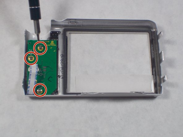 Remove the back of the camera case and place it on a flat surface with the selector button circuit board facing up.