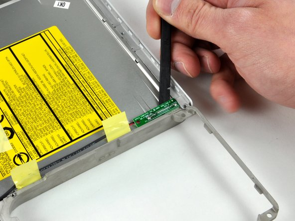 Use a spudger to pry up the Reed Switch Board from the optical drive, removing tape as necessary.