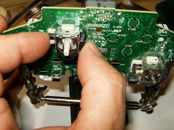 Image 3/3: Place the new analog stick through the holes on the board. Make sure that it is flush with the board.