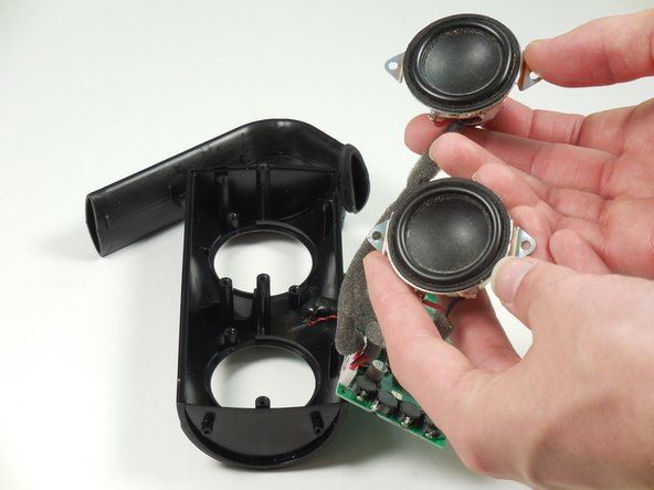 Remove two screws on each speaker.