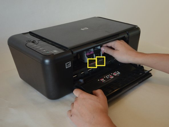 Slide the ink carriage until the the cartridges line up with the marked slots in the middle.