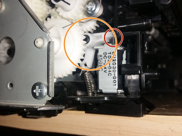 The orange circled rocker is supposed to move once for every page spooled and momentarily press the button circled in red. When the lubricant between the gears mixes with dust it becomes sticky and the rocker does not behave as it should.