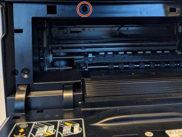 Remove the 11.6mm T9 screw from the top left of the front of the printer.