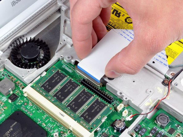 Release the optical drive ribbon clamp as described above. Slide the optical drive ribbon out of its connector.