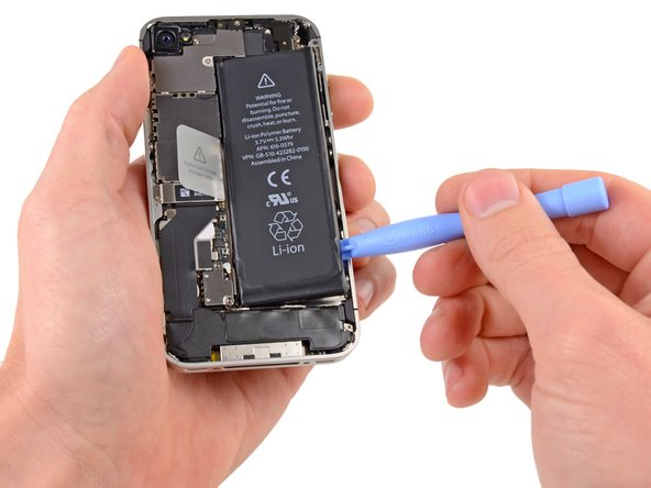 Insert the edge of a plastic opening tool between the battery and the outer case near the bottom of the iPhone.