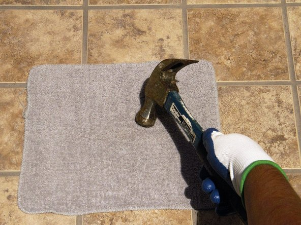 If the tile does not lift, place an old rag over the tile and use the hammer to break the tile into smaller pieces.