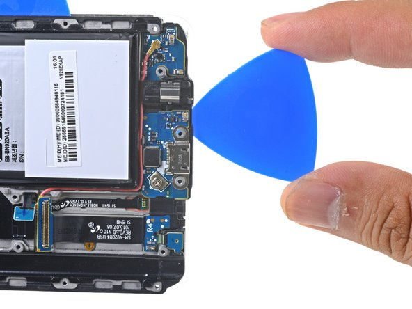 Insert a pick no more than 0.25 inches (~6 mm) into the bottom edge of the phone.