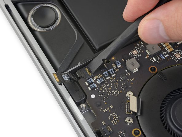 Flip open the locking flap for the right-side main speaker ZIF connector by prying it straight up from the logic board.