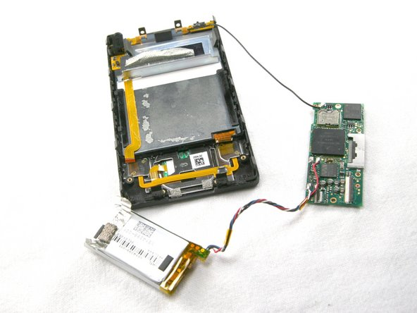 Image 3/3: Remove the mother board from the Zune, leaving the black wire connected.