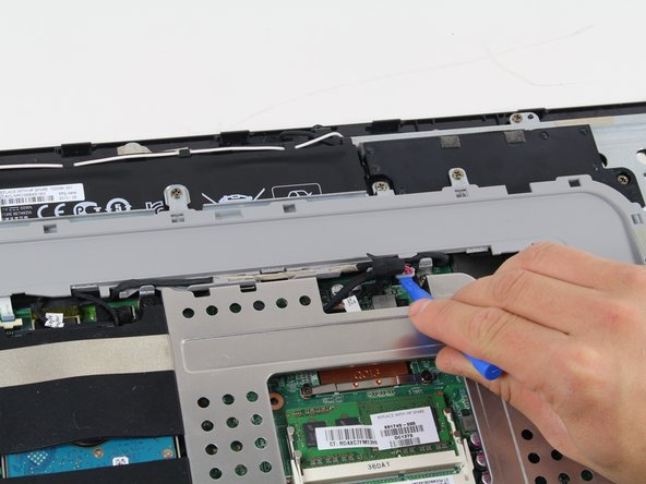 Image 1/2: Disconnect the battery by using a plastic opening tool and taking the cable connection out.