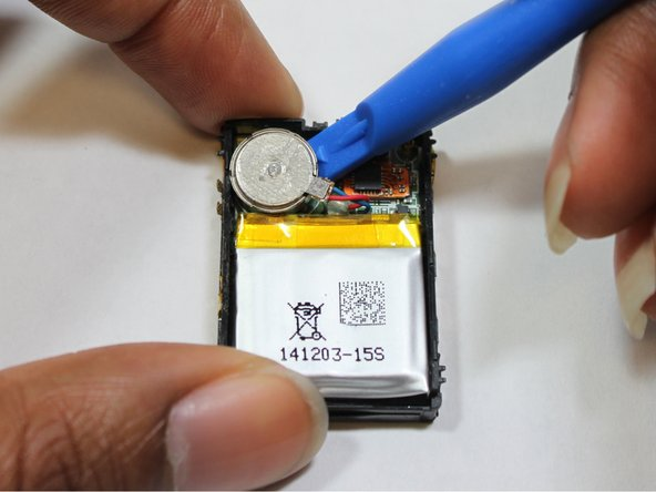 Use a small plastic opening tool to remove the vibration motor from the motherboard.