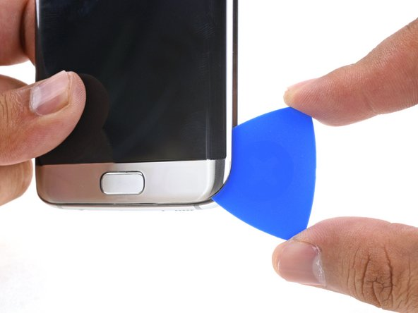 Push the pick in slowly. Try to leverage the pick's cutting edge upward so that it slides against the back of the display.