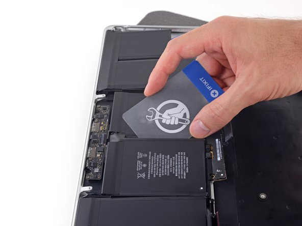 Slide the card farther underneath the battery cell to slice through the adhesive securing it in place.