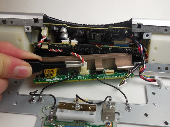 Use the plastic opening tool to remove wires connected to the circuit board on the far right.