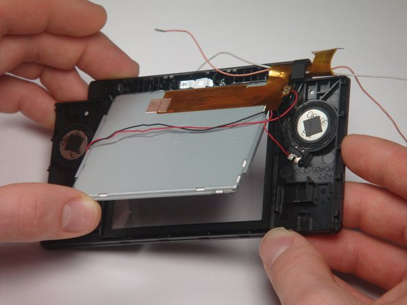 Lift the top LCD out of the plastic frame. Carefully thread the ribbon cable out of the hinge to avoid damaging it.