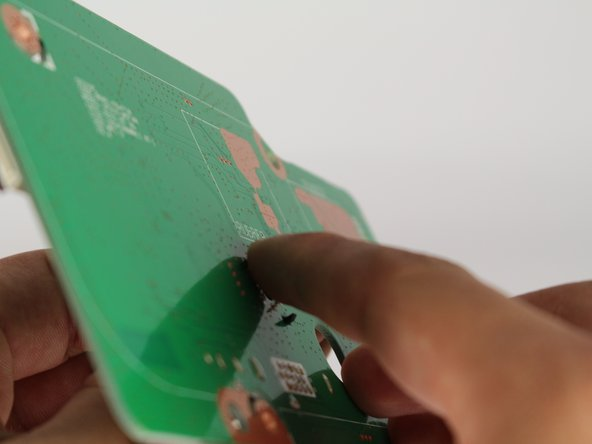 Squeeze the rear tabs located on the back of the motherboard with your thumb and index finger.