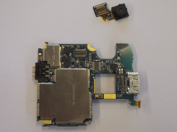 Image 2/2: Pull upwards on the blue rectangle where the gold ribbon ends. This will remove the camera from the circuit board.