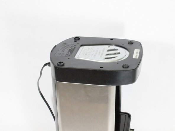 Flip the coffee maker over so the bottom is facing upwards.