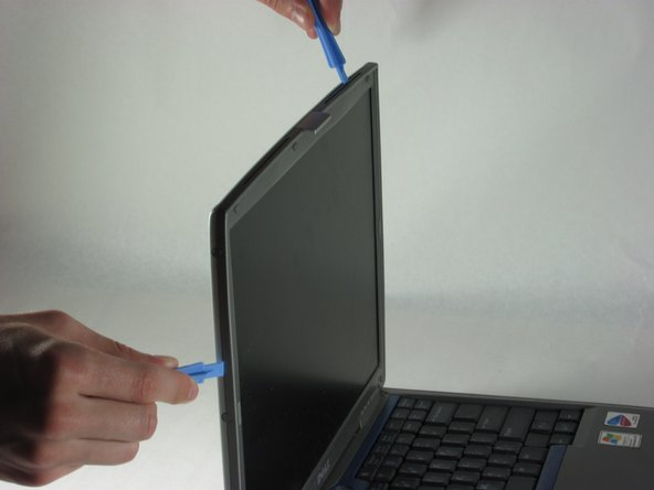 After removing the screws under the rubber dots, use your plastic opening tool to un-clip the plastic around the screen.