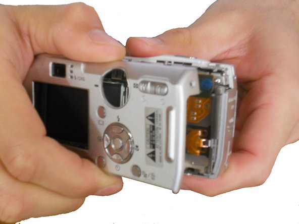 Carefully separate the front casing from the camera body.