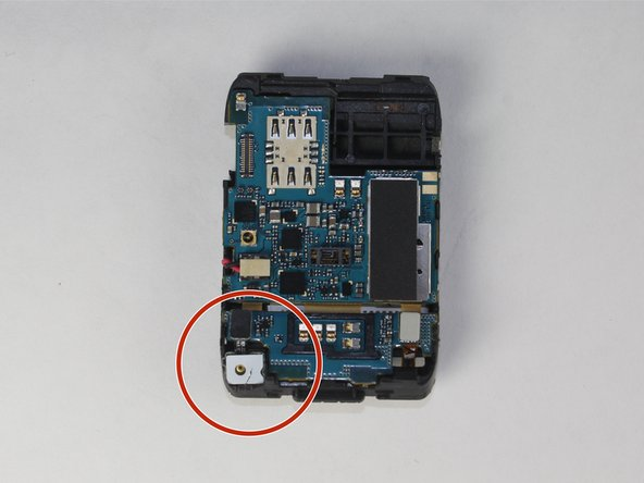 Locate the microphone on the lower right corner of the plastic motherboard assembly .