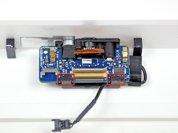 Image 1/1: In the next step, you will rotate the two black retaining clips (shown in red) away from the camera board to free it from the front bezel.