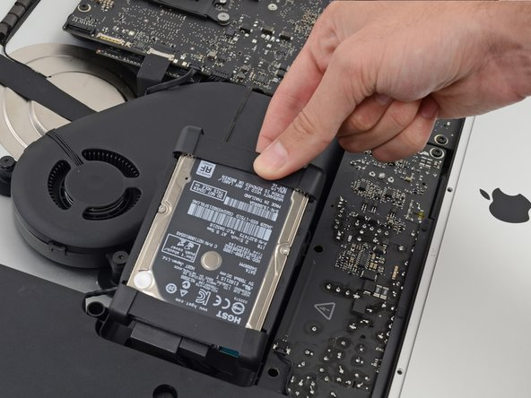 The hard drive is attached by two cables, do not attempt to fully remove it from the iMac just yet.