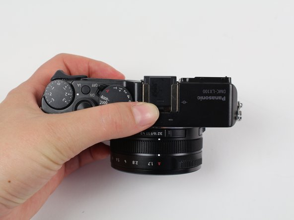 Image 1/3: Remove the small metal insert that rests beneath the black plastic piece by pulling outward, away from the lens side of the camera.